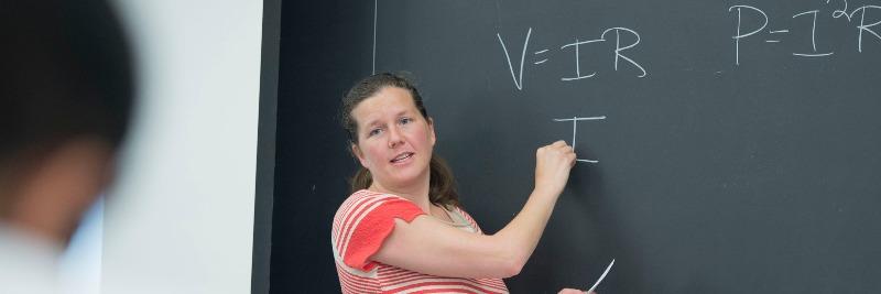 Professor Libby Bucholz teaches an undergraduate class at a chalkboard