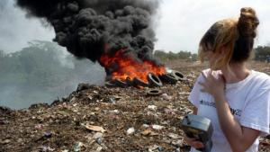 Heidi Vreeland stands in front of a trash fire