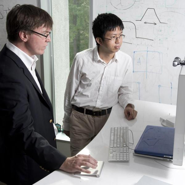 Professor John Dolbow and graduate student Yinglie Liu look at research on a computer screen